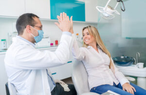 Female patient at the dentist giving a high-five and looking very happy with her smile design